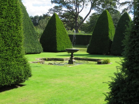 Pyramidenförmig geschnittene Bäume im Garten. Eigenes Foto.