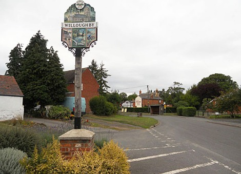 Willoughbys Village Sign, im Hintergrund der letzte verbliebene Pub des Dorfes, The Rose Inn, an der Main Street.    © Copyright Row17 and   licensed for reuse under this Creative Commons Licence.
