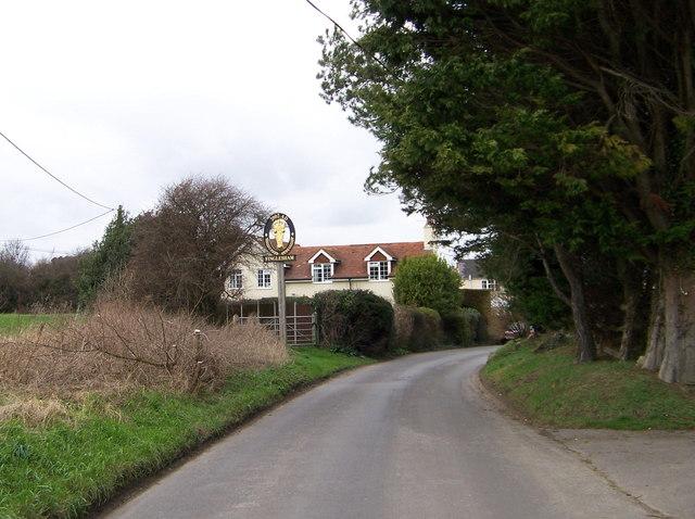 Das Village Sign heißt die Besucher des kirchenlosen Dorfes willkommen.   © Copyright Elliott Simpson and   licensed for reuse under this Creative Commons Licence.