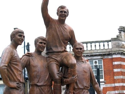 Die Statue in der Nähe des ehemaligen Stadion von West Ham United mit Martin Peters, Geoff Hurst, Bobby Moore und Ray Wilson. This work has been released into the public domain.